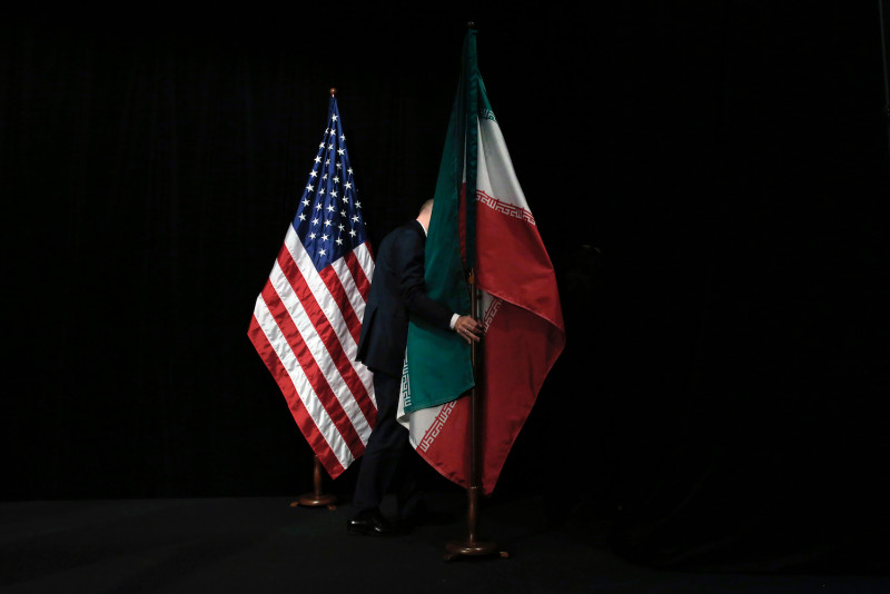 News Agency in MI | A staff member positions an Iranian flag on a stage after a group picture during the Iran nuclear talks at Vienna International Centre in Austria on July 14, 2015.
