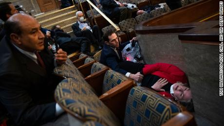 US Rep. Jason Crow comforts Rep. Susan Wild while taking cover as protesters disrupt the joint session of Congress to certify the Electoral College vote on January 6, 2021.