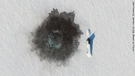 A Russian Delta IV submarine photographed on top of ice near Alexandra Island on March 27, during an exercise, with a likely hole blown in the ice to its left from underwater demolition.