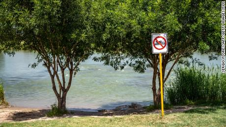 "This file photo from 2019 shows a ""No Swimming"" sign near the Rio Grande in Piedras Negras, Mexico. The mother we met told us her family was on the banks of the river in Piedras Negras when they decided to separate."