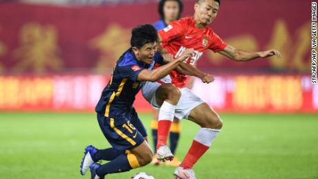 Chen Junle (left) of Guangzhou City fights for the ball with Huang Bowen of Guangzhou FC during the opening match of the new Chinese Super League season.