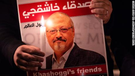 A demonstrator holds a poster picturing Saudi journalist Jamal Khashoggi and a candle during a gathering outside the Saudi Arabia consulate in Istanbul, on October 25, 2018.