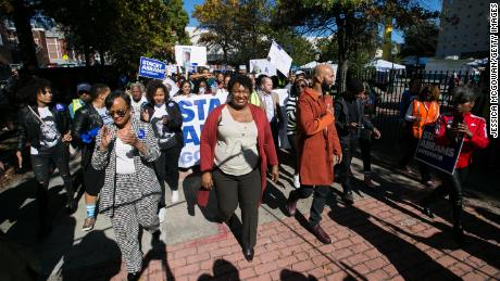 """Then-Georgia Democratic gubernatorial candidate Stacey Abrams and Grammy-winning artist Common lead voters during a """"souls to the polls"""" event in downtown Atlanta on October 28, 2018."""