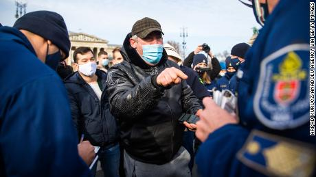 Police officers check a demonstrator during an anti-lockdown demonstration in Budapest, Hungary, on January 31, 2021.