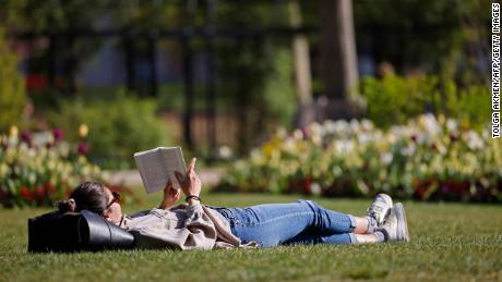 We can read, just as a woman reads a book on the grass in Hyde Park in London on April 23.