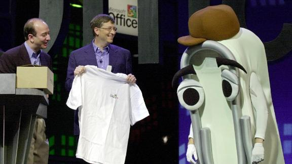 Bezos looks on as Microsoft CEO Bill Gates presents a T-shirt as a retirement gift to Clippy, the Microsoft Office assistant, in 2001. Microsoft was launching Office XP.
