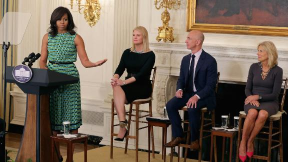 Bezos listens to first lady Michelle Obama at a White House event in 2016. The event announced commitments from more than 50 companies to hire and train veterans and military spouses. Bezos announced a commitment by Amazon to hire 25,000 more military veterans in the next five years.