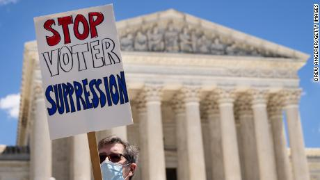 """Activists rally against Sen. Mitch McConnell (R-KY) and Sen. Joe Manchin (D-WV), calling on them to eliminate the legislative filibuster and pass the """"For The People"""" voting rights bill, outside the US Supreme Court on June 23, 2021."""