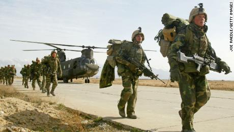 US Army soldiers from the 10th Mountain and the 101st Airborne units disembark from a Chinook helicopter March 11, 2002 as they return to Bagram airbase from the fighting in eastern Afghanistan.