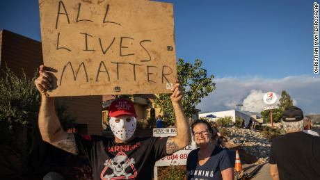 """A man holds an """"All Lives Matter"""" sign at a pro-Trump demonstration on August 1, 2020, in Yucaipa, California."""