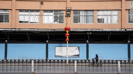 Residents walk in front of a closed of Huanan seafood market on February 9, 2021 in Wuhan, Hubei Province, China.