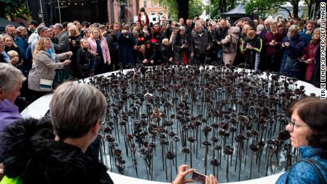 """People stand next to the """"Iron roses"""" memorial outside Oslo Cathedral on September 28, 2019, to commemorate the 77 victims of Anders Behring Breivik's attacks."""