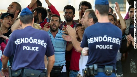 Hungarian police officers face a group of Syrian migrants on the platform of the Kobanya-Kispest station, Budapest suburb, on September 2, 2015, as the refugees refused to board a train to the Debrecen camp.