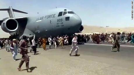 Hundreds of people run alongside a U.S. Air Force C-17 transport plane as it moves down a runway of the international airport, in Kabul, Afghanistan, Monday, Aug.16. 2021.