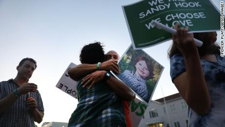 Mark Barden gets a hug while holding up a picture of his son Daniel, who was killed inside Sandy Hook Elementary Schools on December 14, 2012.