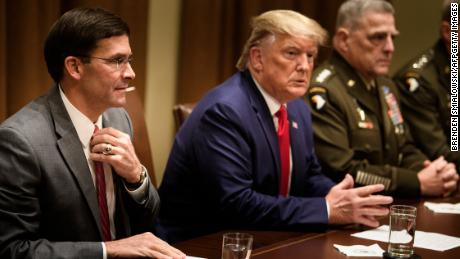 US Secretary of Defense Mark Esper (left), US President Donald Trump, and Chairman of the Joint Chiefs of Staff Army General Mark A. Milley (right) wait for a meeting with senior military leaders in the Cabinet Room of the White House in October 2019.