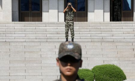 A North Korean soldier looks toward the south as a South Korean soldier stands guard in the truce village of Panmunjom