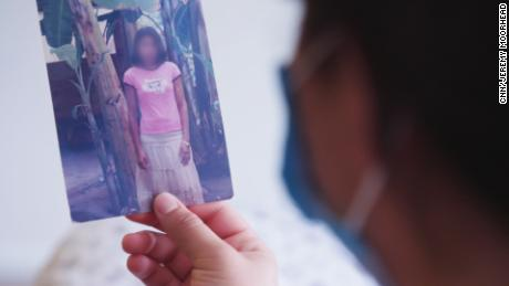 Montserrat looks at a photo of her mom when she was 24 years old. The daughters would fight over who could keep it in their room.