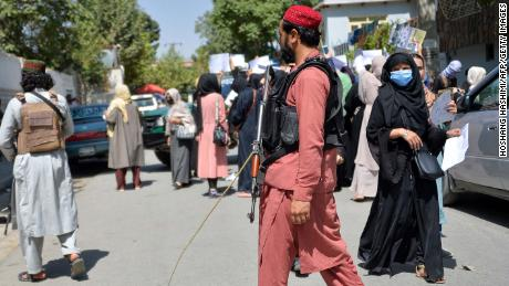 Taliban fighters watch as Afghan women take part in an anti-Pakistan demonstration near the Pakistan embassy in Kabul on Tuesday.