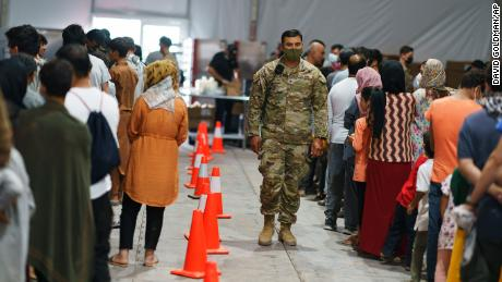 Afghan refugees line up for food in a dining hall at Fort Bliss' Doña Ana Village where they are being housed in Chaparral, N.M., Friday, Sept. 10, 2021.