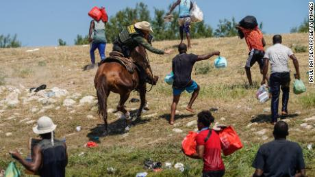 A US Border Patrol agent on horseback tries to stop a Haitian migrant from entering an encampment on the banks of the Rio Grande near the Acuna Del Rio International Bridge in Del Rio, Texas, on September 19, 2021.