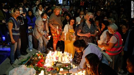 People place candles at a vigil for murdered 28-year-old teacher Sabina Nessa in Kidbrooke in south-east London, September 24, 2021. (AP Photo/David Cliff)
