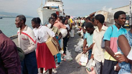 Haitian refugees disembark from a US Coast Guard vessel in February 1992 after being  deported from Guantanamo Bay, Cuba.